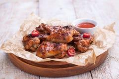 Las alas de pollo asadas de la barbacoa con el Bbq sauce, las hierbas, aceite de oliva y pimienta italianos Foto de archivo libre de regalías