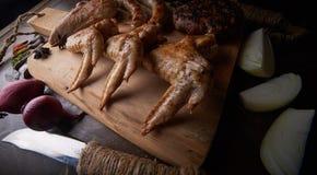 Las alas de pollo asan a la parrilla el fondo de la comida, fondo de madera Imagenes de archivo