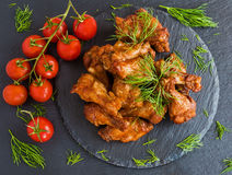 Las alas de pollo cocinaron con la salsa de barbacoa en fondo de piedra negro Pequeños tomates y eneldo de cereza Visión superior Imagen de archivo libre de regalías
