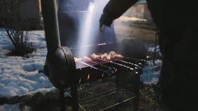 Las alas de pollo se cocinan en la parrilla y al mismo tiempo agitar un accesorio para mantener la temperatura metrajes
