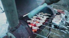 Las alas de pollo se cocinan en la parrilla y al mismo tiempo agitar un accesorio para mantener la temperatura Cámara lenta metrajes