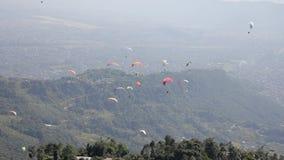 Las alas flexibles en los paracaídas coloridos vuelan sobre la ciudad en un valle verde de la montaña