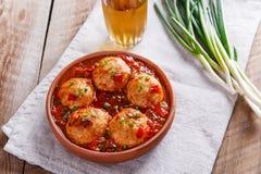 Las albóndigas del pollo con la salsa de tomate en una arcilla ruedan fotos de archivo