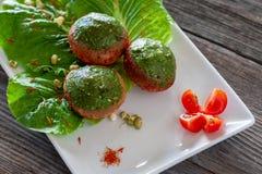 Las albóndigas vegetarianas del champiñón con la salsa del Pesto en un blanco plat foto de archivo libre de regalías