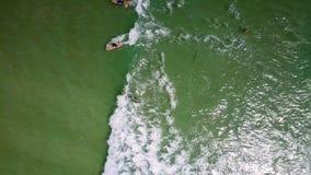 Las altas personas que practica surf superiores de la visión nadan en ondas espumosas metrajes