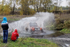 Las alzas de SUV del deporte riegan el obstáculo rodeado cerca salpican Foto de archivo libre de regalías
