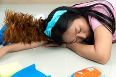 Las amas de casa asiáticas mienten en el piso debido cansarse de tareas de hogar Con el diverso equipo de limpieza colocado alred fotografía de archivo