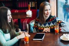 Las amigas comunican en un café Imagen de archivo libre de regalías