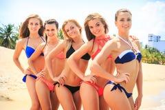 Las animadoras del primer en bikinis se colocan de cerca en línea en la playa Imagenes de archivo