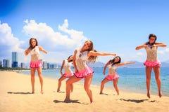 Las animadoras en danza plantean las manos a un lado en la playa contra el mar Imagen de archivo