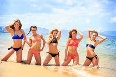 Las animadoras presentan en la línea manos hacia arriba en la playa contra el mar Fotos de archivo
