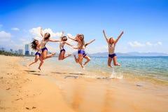 Las animadoras saltan síncrono sobre sonrisa del agua poco profunda Foto de archivo libre de regalías