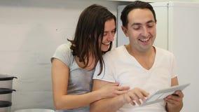 Las aplicaciones felices de los pares hacen tabletas mientras que se sientan en la tabla de cocina metrajes