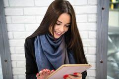 Las aplicaciones hermosas jovenes de la empresaria del estudiante de la empresaria hacen tabletas al aire libre fotos de archivo libres de regalías