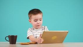 Las aplicaciones lindas del niño pequeño hacen tabletas sentarse en la tabla, aislada en azul almacen de metraje de vídeo