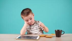 Las aplicaciones lindas del niño pequeño hacen tabletas sentarse en la tabla, aislada en azul almacen de video