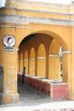 Las arcadas amarillas enmarcan el lavadero al aire libre en Antigua Guatemala Imágenes de archivo libres de regalías