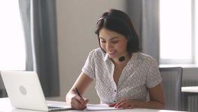 Las auriculares que llevan de la empresaria asiática hacen charla de las notas por audioconferencia metrajes