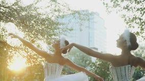 Las bailarinas de la elegancia bailan en la puesta del sol en parque almacen de metraje de vídeo