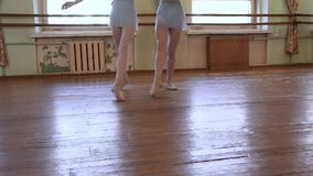 Las bailarinas en leotardos azules hacen ejercicios en pares durante clase del ballet almacen de metraje de vídeo