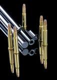 Las balas de cobre amarillo en el extremo de un rifle barrel Imagenes de archivo