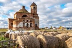 Las balas de heno en el primero plano en el fondo dilapidaron iglesia vieja desde el imperio ruso imagen de archivo