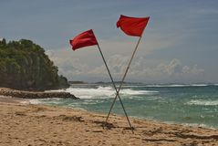 Las banderas cruzadas rojo en la playa significan una prohibición para nadar Foto de archivo
