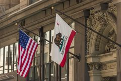 Las banderas de los Estados Unidos y de la California en un edificio en el distrito financiero de San Francisco, California, los  fotos de archivo