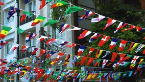 Las banderas de los países diferentes cuelgan en las calles de la ciudad almacen de metraje de vídeo