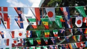 Las banderas de los países diferentes se cuelgan en el aire sobre la calle El concepto del acontecimiento deportivo del mundo almacen de video