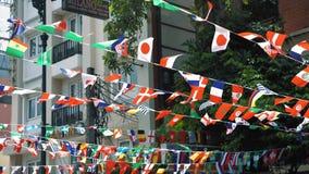 Las banderas de muchos países cuelgan en cuerdas en el aire en el fondo de la ciudad almacen de video