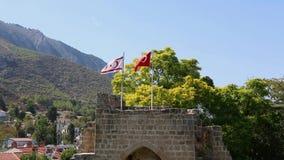 Las banderas de Turquía y de Chipre septentrional están agitando sobre la abadía de Bellapais almacen de video