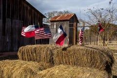 Las banderas del americano y de Tejas arreglaron en las balas de la paja, decoración del Día de la Independencia Imagen de archivo
