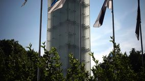 """Las banderas nacionales de Estonia contra la perspectiva de """"monumentde la libertad"""" en cuadrado de la libertad, se dedican a almacen de video"""