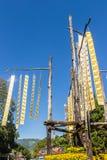 Las banderas tailandesas septentrionales tradicionales hermosas de la tribu están colgando en los polos con el fondo del cielo az Foto de archivo