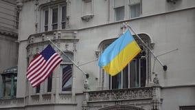 Las banderas ucranianas y americanas están agitando almacen de metraje de vídeo