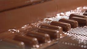 Las barras de caramelo se vierten con el chocolate líquido Primer metrajes