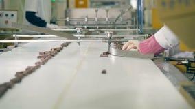 Las barras de chocolate se están moviendo lentamente a lo largo de la banda transportadora después de ser clasificada por los tra almacen de metraje de vídeo
