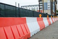 Las barreras plásticas anaranjadas y blancas del jersey protegen una construcción imágenes de archivo libres de regalías