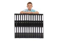 Las bases del muchacho en muchas carpetas negras grandes Fotos de archivo libres de regalías