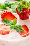 Las bayas y las rebanadas de la fresa y las hojas de menta fresca adornan el yogur de la fresa en un cierre del vidrio para arrib Fotografía de archivo