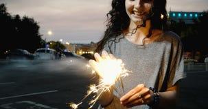 Las bengalas ardientes sonrientes felices de la muchacha en calle de la noche con fuera de la ciudad del foco se encienden detrás almacen de video