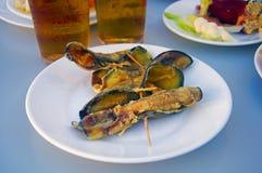 Las berenjenas fritas rodaron para arriba con los camarones dentro, dos cervezas imagenes de archivo