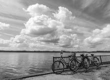 Las bicicletas al lado del lago riegan debajo del cielo extenso imagen de archivo libre de regalías