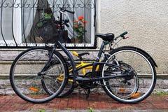 Las bicicletas del adulto y de los niños parquearon contra la pared Fotografía de archivo libre de regalías