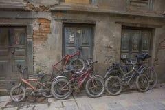 Las bicicletas lamentables viejas de diversos tamaños se colocan en la calle cerca de la pared dañada imágenes de archivo libres de regalías