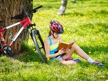 Las bicis que completaban un ciclo el casco que llevaba de la muchacha leyeron el libro en resto cerca de la bicicleta Fotos de archivo libres de regalías