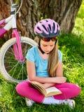 Las bicis que completaban un ciclo el casco que llevaba de la muchacha leyeron el libro en resto cerca de la bicicleta Imagen de archivo libre de regalías