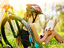 Las bicis que completaban un ciclo el casco que llevaba de la muchacha leyeron el libro en resto cerca de la bicicleta Foto de archivo libre de regalías