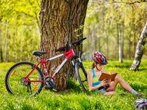 Las bicis que completaban un ciclo a la muchacha leyeron el libro en resto cerca de la bicicleta Fotos de archivo libres de regalías